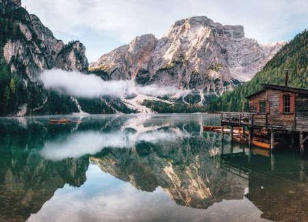 Panoramic view of Braies Lake with the hut and boats in Dolomites mountains and Seekofel in the morning, Pragser Wildsee, South Tirol, Italy