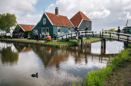 Zaanstad, Netherlands - 26 April, 2017: Authentic Zaandam mills and traditional vibrant houses on the water canal in Zaanstad village, Zaan river, Netherlands Editorial