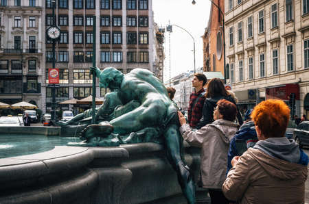 Vienna, Austria - 1 October, 2017: Woman tourist caresses back of statue of Ancient god for luck. Donnerbrunnen Fountain at Neuer Markt square in Vienna, Austria. Redakční