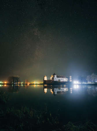 Mir, Belarus - December 13, 2017: Scenic view of Mir Castle at night with starry sky and glow reflexion on lake. Landmark in Belarus Éditoriale