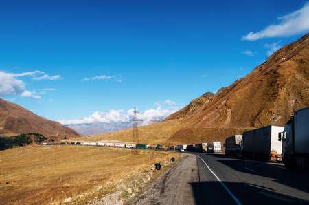 Stepantsminda, Georgia - October 10, 2016: Trucks line up in 20 km queue at Georgia-Russia border. Georgian Military Road
