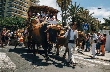 プエルト・デ・ラ・クルス、テネリフェ島、カナリア諸島、スペイン - 2017年5月30日:伝統的な服を着た装飾された雄牛が描かれたワゴンとカナリアの人々がパレードに参加します。テネリフェ島はカナリア諸島の日を祝います。