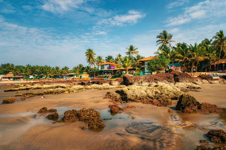 Guesthouses and sunbeds on the shore of the Arabian Sea in the middle of rocks and sandstone in Ashvem, Goa, India
