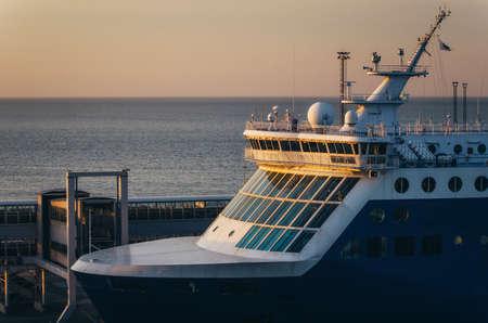 Close up view of ferry wheelhouse with large windows, antennas, megaphone against passenger gate Stock Photo