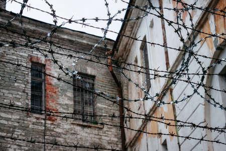 Tallinn, Estonia - July 1, 2013: Old ramshackle decrepit walls through barbed wire fence. Old Soviet Prison Editorial