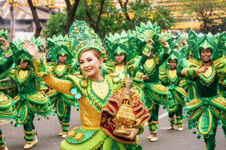 Cebu City , The Philippines - January 20, 2019: Street dancers in vivid colorful costumes participate in the parade at the Sinulog Festival. 新闻类图片