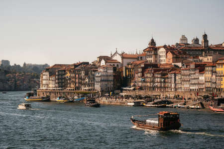 Old town of Porto on Douro River with tourist boats and ferry at sunset, Portugal. 写真素材