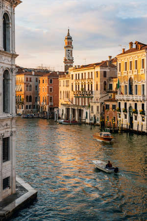 Gondolas and boats float on Grand Canal at sunset in Venice, Italy. View from Rialto Bridge Banco de Imagens
