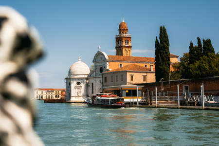 Vaporetto water bus station against San Michele in Isola church with tower in Laguna Nord, Venice