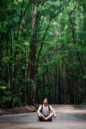 Man with backpack sits on road through green Bilar Man-Made Forest, Bohol, Philippines