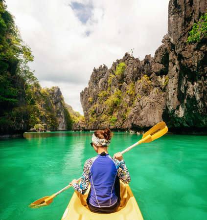 Rear view of young woman moves on water in kayak using paddle against cliffs in El Nido, Palawan, Philippines.