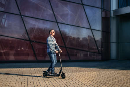 Man riding a electric kick scooter on stone pavement against modern glass wall of building Imagens