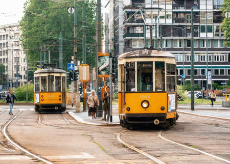 Milan, Italy - May 7, 2019: Vintage yellow tram on typical street of Milan