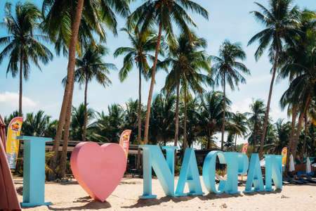 Nacpan beach, Palawan, Philippines - February 1, 2019: View of the blue and pink I love Nacpan sign on beach against palm trees, Palawan, Philippines