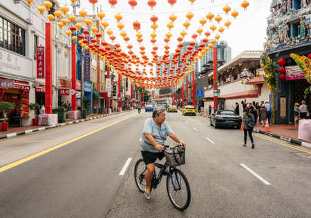 Chinatown, Singapore - February 8, 2019: Old man rides bike on South Bridge Road near Sri Mariamman Temple in Chinatown district with colorful lanterns for Chinese New Year