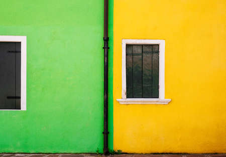View of green and yellow stone house and small white windows with wooden shutters. Minimalism and free space for background concept.
