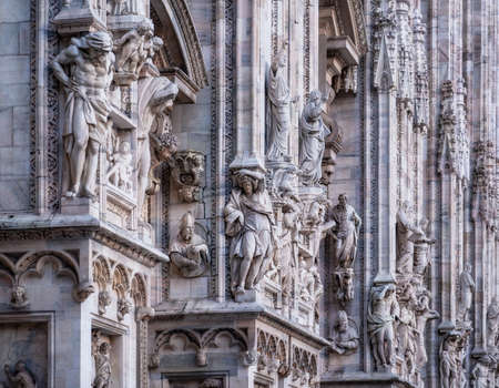 Facade of Duomo Cathedral with details, statues and marble works, Milan, Italy,