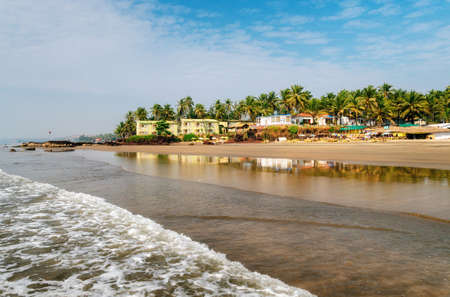 Guesthouses and sunbeds on beach of Arabian Sea in middle of rocks and sandstone in Ashvem, Goa, India
