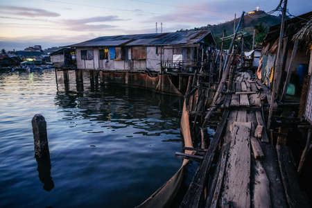 Poor district slums with wooden houses near water at dusk, Coron city, Palawan, Philippines