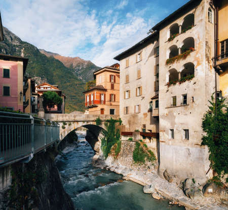 Scenic view on small river flowing through gorge between houses in cute town of Chiavenna, Italy. Imagens