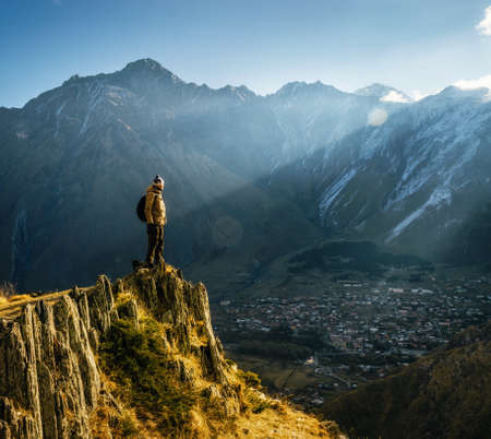 Young tourist in bright hat, black trousers with a backpack stands on cliffs edge and looking at the misty mountain village and glacier at sunrise, Stepantsminda, Georgia Imagens