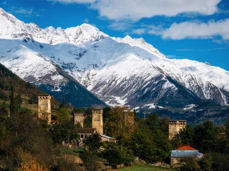 View of the Svanetian towers in Mestia village against mountains with glaciers snow peaks. Upper Svaneti, Georgia. Georgian landmark Imagens