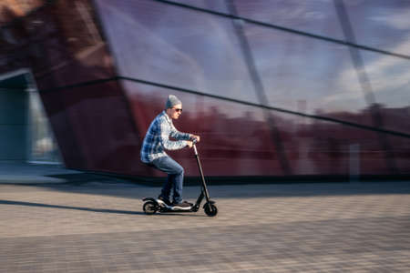 Young man in casual wear on electric kick scooter on city street in motion blur against modern glass office building
