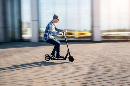 Young man in casual wear on electric kick scooter on city street in motion blur in sunday Imagens