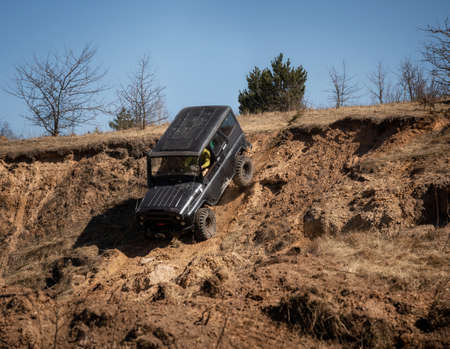 4x4 suv truck driving downhill on edge of hill. Off road concept