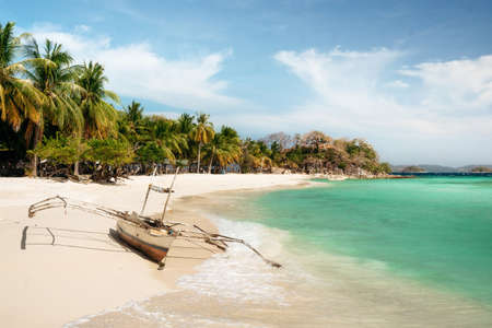 Tropical Malcapuya island with traditional philippines bangka boat, azure water and white sand beach. Travel vacation at Philippines.