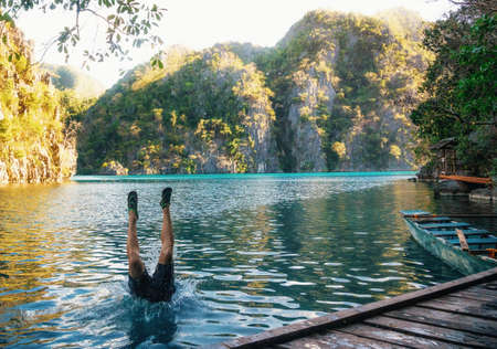 Young man jumps to lake. Legs stick out of water. Kayangan lake, Coron, Philippines