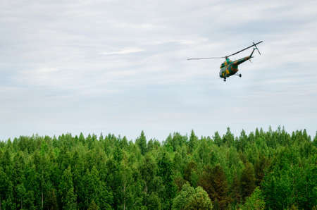 Khaki colored helicopter is flying in blue sky above forest Imagens