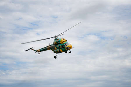 Khaki colored helicopter is flying in blue sky