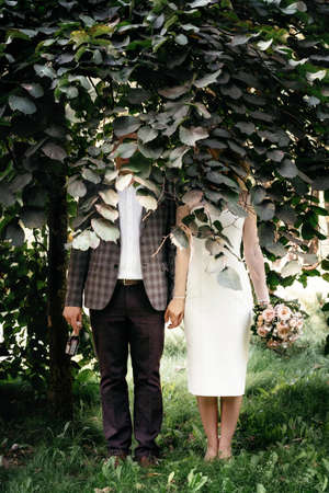 Wedding couple stands under green tree with faces hidden by foliage and hold hands