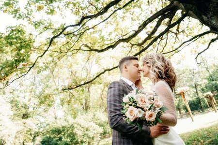 Portrait of kissing couple in the garden against huge oak