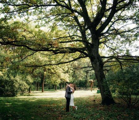 Portrait of kissing couple in the garden under huge oak Imagens