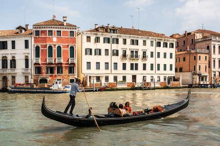 Venice, Italy - May 10, 2019: Venetian gondolier punts gondola through narrow canal waters of Venice Italy
