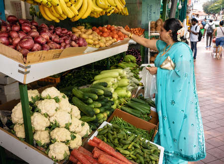 Chinatown, Singapore - February 9, 2019: Indian woman in saree buys fruits and vegetables at the market in Little India, Singapore