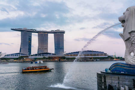 Singapore - February 8, 2019: Tourist boat sails against Merlion statue fountain against and Singapore city skyline with Marina Bay Resort at sunset Redakční