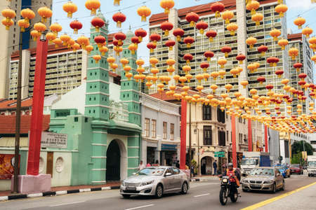 Chinatown, Singapore - February 8, 2019: cars and people on South Bridge Road near Sri Mariamman Temple in Chinatown district with colorful lanterns for Chinese New Year