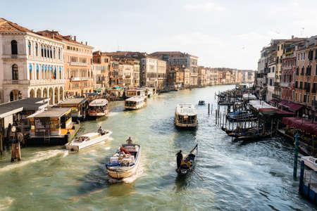 Venice, Italy - May 9, 2019: Cargo boat, gondola, vaporetto float across Canal Grande, Venice Italy