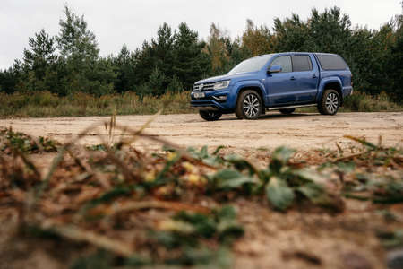 Minsk, Belarus - September 20, 2019: Volkswagen Amarok 4x4 pickup truck on country road at woodland. Editorial
