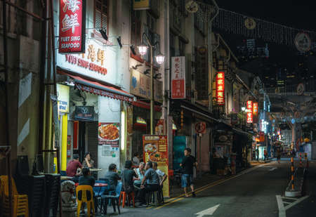 Singapore - February 8, 2019: Chinese people have dinner in street cafe at night in Chinatown