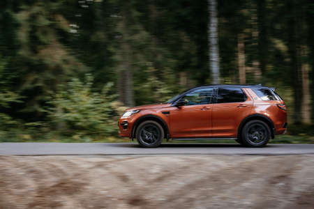 Minsk, Belarus - September 24, 2019: borwn color car Land Rover Discovery Sport fast moving on country road in green autumn forest.