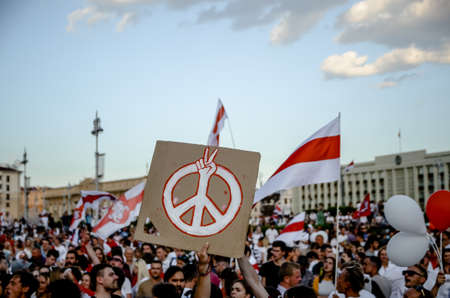 Minsk, Belarus - August 16, 2020: Belarusian people participate in peaceful protest after presidential elections in Belarus. Person holds peace sign banner at protest