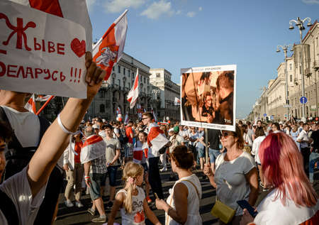 Minsk, Belarus - August 16, 2020: Belarusian people participate in peaceful protest after presidential elections in Belarus. Woman holds poster with photo of victim of violence by riot police.