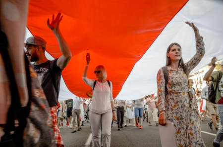 Minsk, Belarus - August 16, 2020: Belarusian people carry giant historical flag of Belarus. They participate in peaceful protest after presidential elections in Belarus Redakční