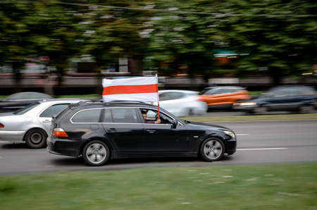 Minsk, Belarus - August 21, 2020: Belarusian people participate in peaceful protest after presidential elections in Belarus. Car passenger holds a white-red-white flag