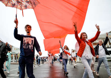 Minsk, Belarus - August 23, 2020: Belarusian people carry giant historical flag of Belarus. They participate in peaceful protest after presidential elections in Belarus Redakční