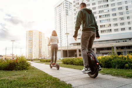 Young man riding unicycle and young woman in casual wear riding on electric kick scooter on city street